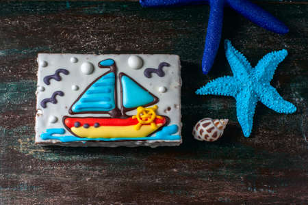 christmas cookie: Homemade homemade gingerbread cookie in the shape of a boat on the dark dark wooden background. Selective focus.