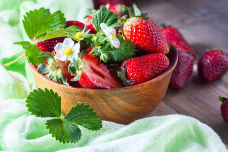 Fresh strawberries in a wooden bowl on a wooden background. Selective focus