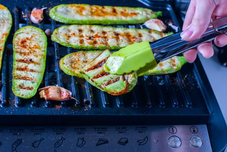 Grilled zucchini on a grill close-up. Closeup of the hands of a young woman. Selective focus Stock Photo