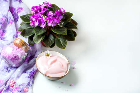 spa setting with cosmetic cream, bath salt and African violet (saintpolia) in flower pot on white wooden table background.