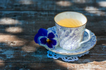 Porcelain cup of tea on a wooden table in the garden. Summer party. Selective focus