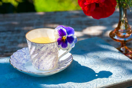 Porcelain cup of tea and beautiful spring flowers in vase on a wooden table in the garden. Summer party. Selective focus