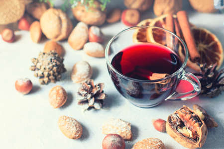 Christmas composition. Glass of red mulled wine on table with cinnamon sticks, Christmas decorations. Selective focus