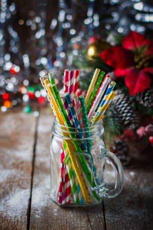 Multicolored spiral straw cocktails in a glass jar Mason on a festive New Years background. Sweet table. A table with a drink. Selective focus