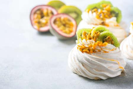 Homemade cake Pavlova with whipped cream, fresh kiwi and passion fruit. Stock Photo