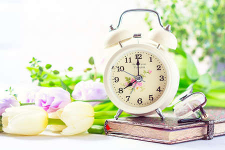 Retro alarm clock, notebook and spring flowers. Selective focus
