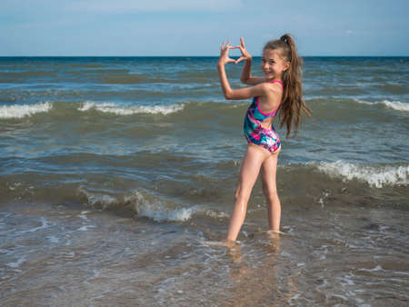 A teenage girl in a bathing suit, swims in the sea. The concept of a healthy lifestyle Imagens
