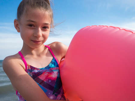 A teenage girl on the beach by the sea with an inflatable big pink circle. Selective focus