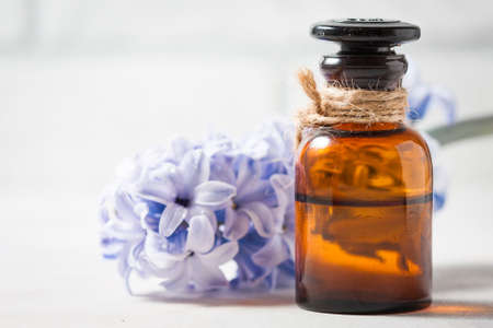 Bottle with essential oil and with lilac flowers on a white background. Macro. Selective focus