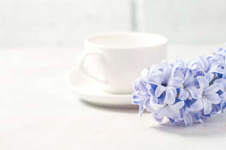 White coffee cup on a white background and flowers. Selective focus Reklamní fotografie