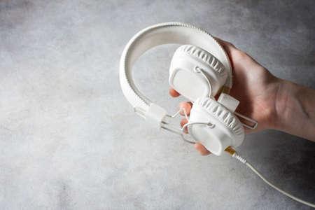 White headphones hold female hands. Selective focus Reklamní fotografie