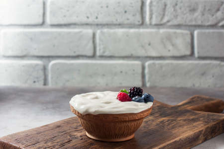 Greek yogurt in a wooden bowl on a rustic wooden table. Selective focus Stock Photo