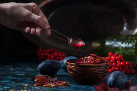 Homemade plum jam and fruit on a wooden table. Childs hand holding a spoon with jam. Selective focus 写真素材