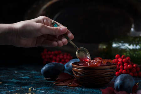 Homemade plum jam and fruit on a wooden table. Child's hand holding a spoon with jam. Selective focus Reklamní fotografie