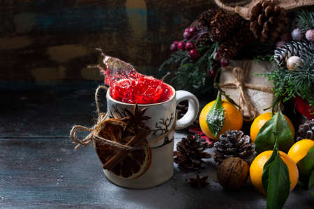Mulled wine splashes and tangerines Christmas composition. Gift box, cones on a dark wooden background. Copy space