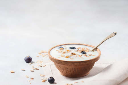Homemade yogurt with granola and berries in a ceramic bowl on a light background. Concept healthy breakfast. 스톡 콘텐츠