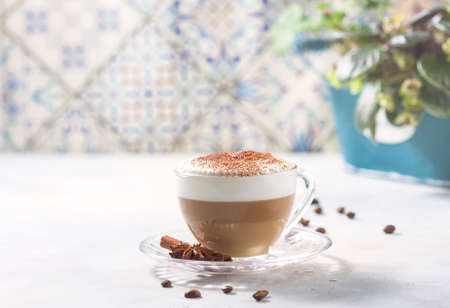 Cappuccino or latte in a glass cup on a light background. Stockfoto