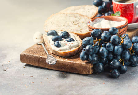 Whole grain bread toasts with ricotta cheese, black grapes on a wooden cutting board. Food concept. Selective focus. Kinfolk Style Stock fotó