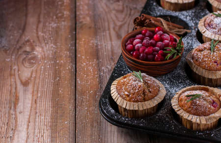Fresh homemade Cranberry muffins in baking form on wooden table with Christmas decoration. Muffins in eco-friendly recyclable paper packaging.