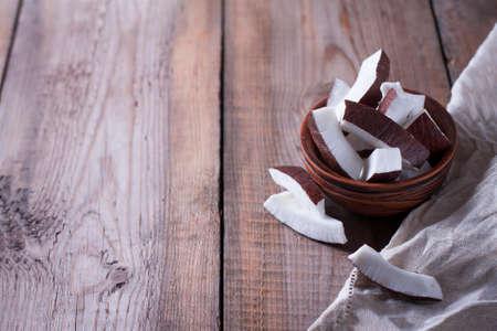 Keramikschale mit Kokosscheiben auf Holzhintergrund. Selektiver Fokus, Kopienraum.