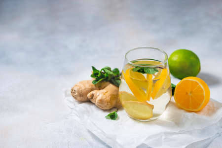 Ginger-lemon drink. Homemade Organic ginger in a glass with Lemon and mint on white table. Trendy detox healthy drink. Selective focus, copy space.
