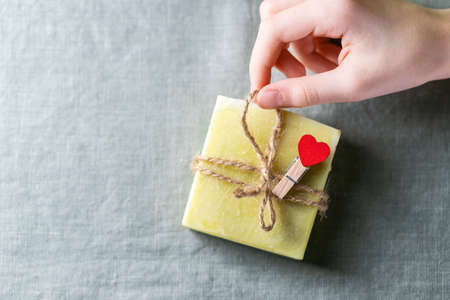 Natural handmade soap with a heart decor on a background of linen fabric. Childrens hands hold natural soap. Foto de archivo