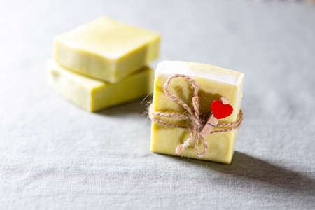 Natural handmade soap with a heart decor on a background of linen fabric.