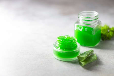 Fresh ?loe vera gel in a glass jar with aloe on a light background. Selective focus, copy space for text. Top view. Stock Photo