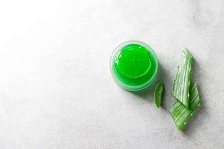 Fresh aloe vera gel in a glass jar with aloe on a light background. Selective focus,copy space for text. Top view.