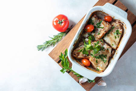 Baked filet of white fish in a white ceramic form on a baked background.