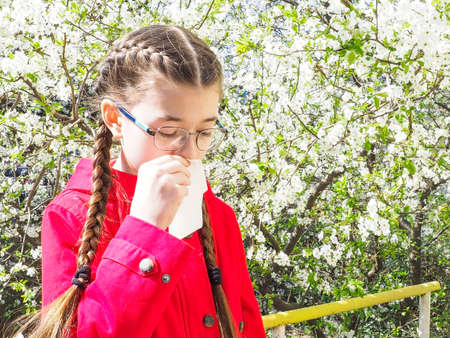 Teen girl suffers from pollen allergy during flowering, uses napkins. Spring allergy concept. Selective focus