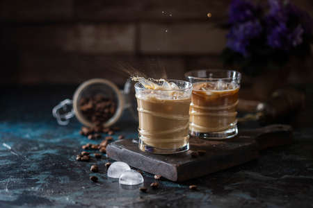 Splash of iced coffee in a glass glass and coffee beans on a brown background. Summer refreshing drink. Selective focus, copy space.