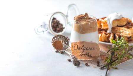 Iced frothy drink Dalgona Coffee, trend korean drink latte espresso with coffee. Gray concrete background. Selective focus, copy space 版權商用圖片