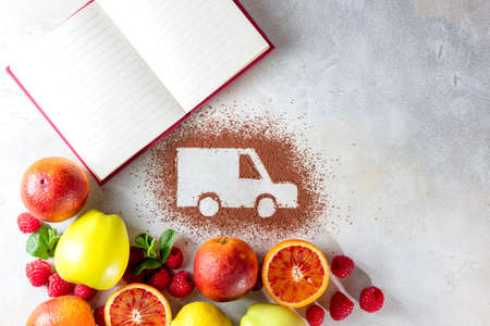 Car made of cocoa powder and citrus fruits on a light background. Online shopping. Healthy nutrition, strengthening immunity. The concept of delivery services, logistics, cargo delivery. Copy space