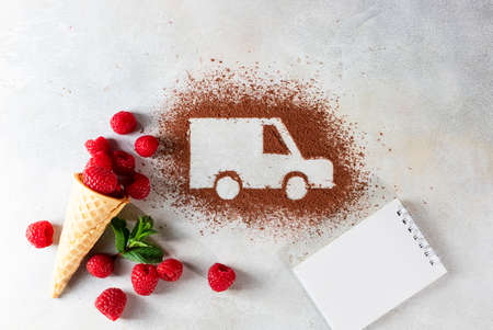 Car made of cocoa powder and raspberries on a light background. Online shopping. The concept of delivery services, logistics, cargo delivery. Copy space Фото со стока