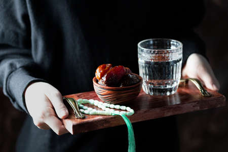 A female hand holds a tray with dates, and water and a rosary - hthe things used to break the fast at sunset during the Muslim holy month of Ramadan. Dark background. Selective focus, place for text. Banque d'images