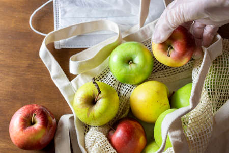 Hand in glove holds apple. Eco mesh bag with food supplies on a wooden background. Food delivery in eco-friendly packaging, zero waste. Flat lay, top view, copy space Фото со стока