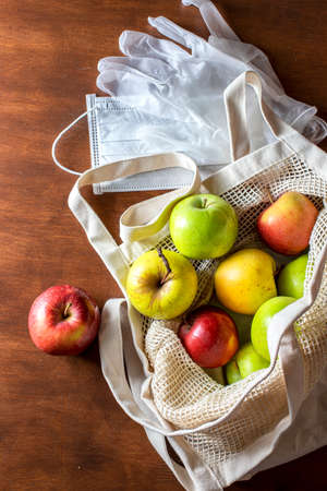 Eco mesh bag with apples supplies on a wooden background. Food delivery in eco-friendly packaging, zero waste. Flat lay, top view, copy space