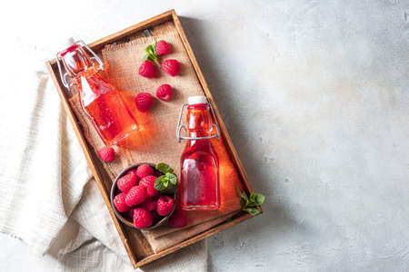Homemade raspberry vinegar and fresh raspberries. Flat lay for your text.