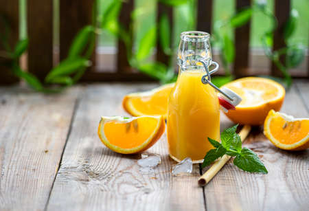Fresh orange juice with oranges fruit outdoors on a wooden table. Front view. Selective focus, copy space