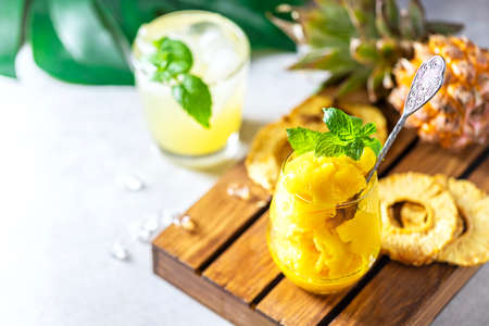 Homemade pineapple sorbet ice cream in a glass on a wooden background. Selective focus, flat Lay Stock fotó