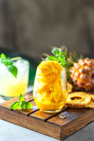 Homemade pineapple sorbet ice cream in a glass on a wooden background. Selective focus Stock fotó