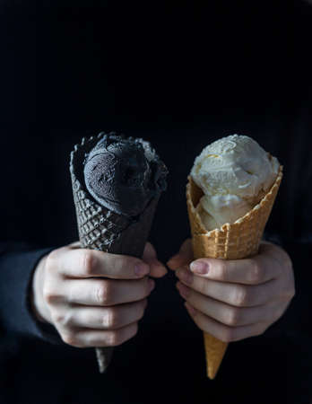 Black ice cream and white ice cream in a waffle cup in female hands. Fashionable food. Copy space Reklamní fotografie