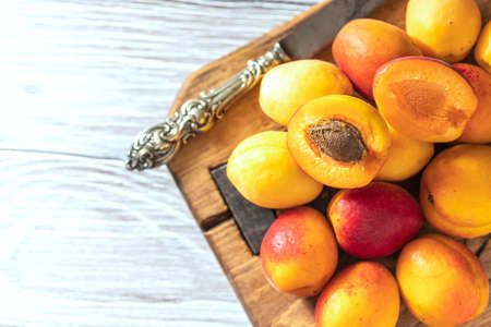 Ripe fresh apricots on a wooden background. Summer fruit concept. Rustic style. Free space for your text. Top view, selective focus