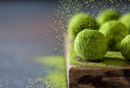Homemade truffle sweets with matcha green tea on a dark background. Raw energy balls. Selective focus, copy space Imagens