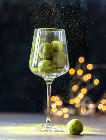Homemade truffle sweets with green matcha tea in a glass goblet on a dark background. Raw energy balls. Selective focus, copy space