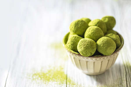 Homemade truffle sweets with green matcha tea in a ceramic bowl on a light wooden background. Raw energy balls. Selective focus, copy space