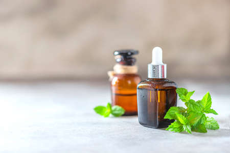 Cosmetics with extract or peppermint oil. Peppermint essential oil and leaves on a light background. Selective focus