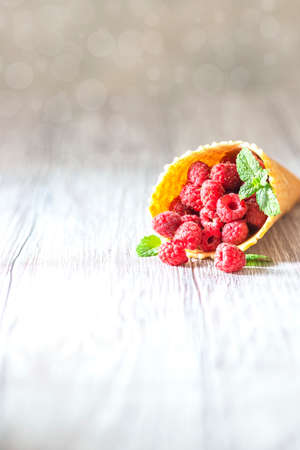 Fresh Raspberries in a waffle cone on a white wooden background. Creative concept, vegan food.