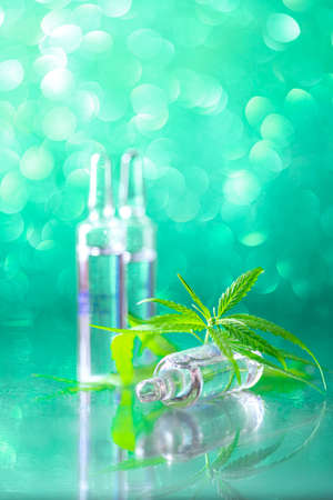 Ampoules on a beautiful bokeh background. Concept of using cannabis herb and leaves for treatment. Alternative treatment. Natural cosmetics. Cosmetology injections.